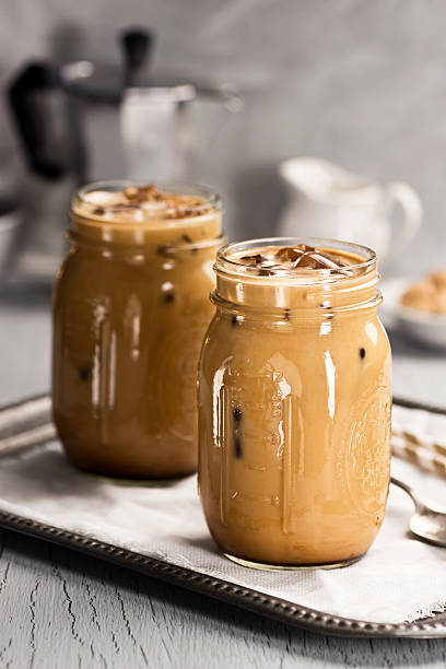 Two mason jars with iced coffee on a silver tray stock photo