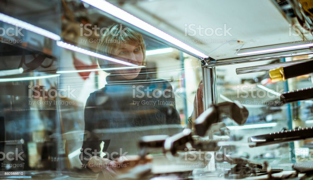 Two mature, 50-years-old women viewing the collection of knives in the storefront royalty-free stock photo