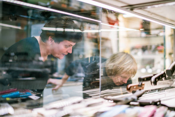Two mature, 50-years-old women viewing the collection of knives in the storefront Two mature, 50-years-old women viewing the collection of knives in the storefront in the small hunting store in Russia, Eastern Europe. gun shop stock pictures, royalty-free photos & images