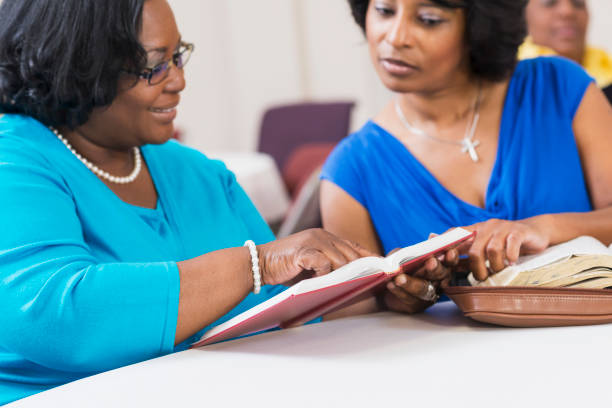 Two mature black women reading and discussing the bible stock photo