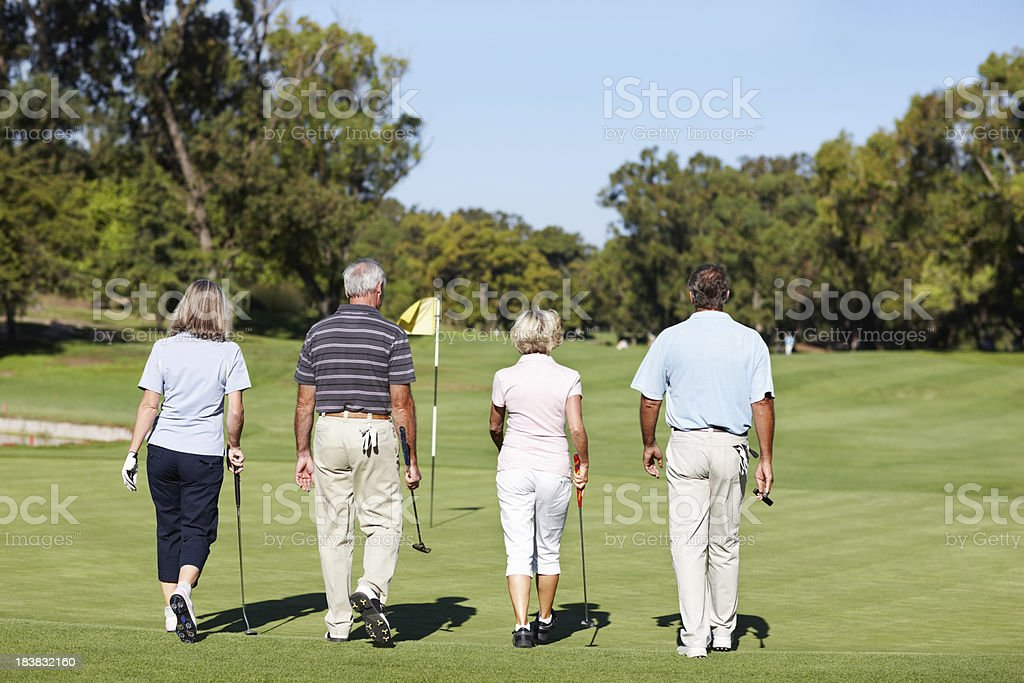 Two mature couples walking on a golf course royalty-free stock photo