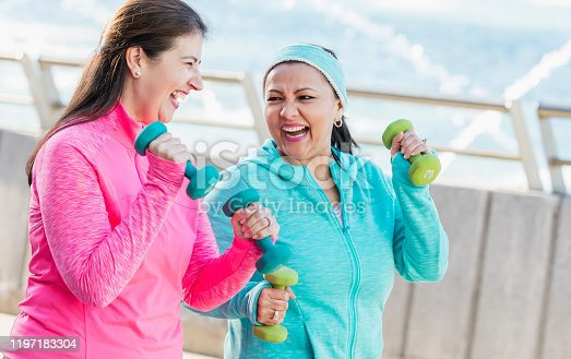 Two mature Hispanic women in their 50s exercising together outdoors, conversing and laughing as they lift hand weights on their walk.