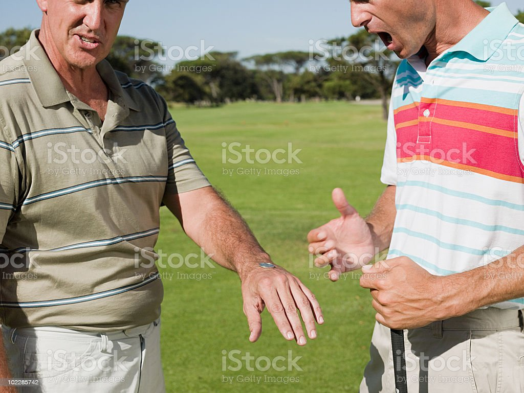 Two mature men playing golf together, tossing a coin stock photo