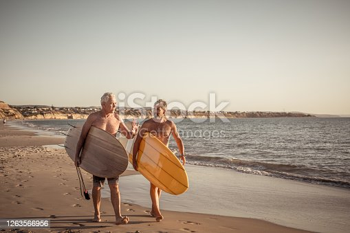 Two mature men walking with surfboards on beautiful beach enjoying paradise and retirement lifestyle. Attractive fit senior adults friends having fun surfing. In real active and healthy people.