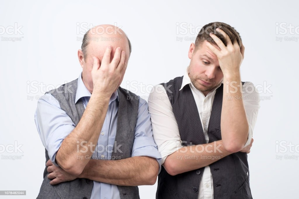 Two mature men with face palm gesture. stock photo