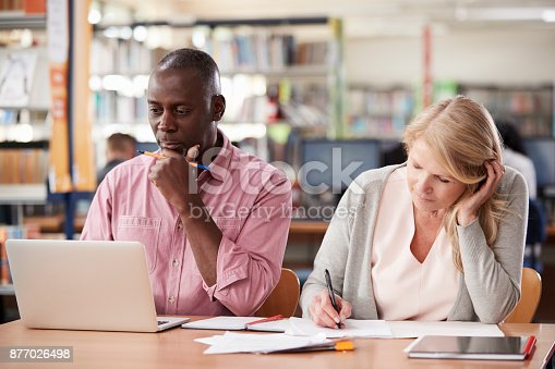 877026364 istock photo Two Mature Students Working In College Library 877026498