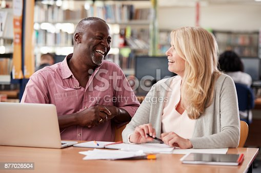 877026364 istock photo Two Mature Students Working In College Library 877026504