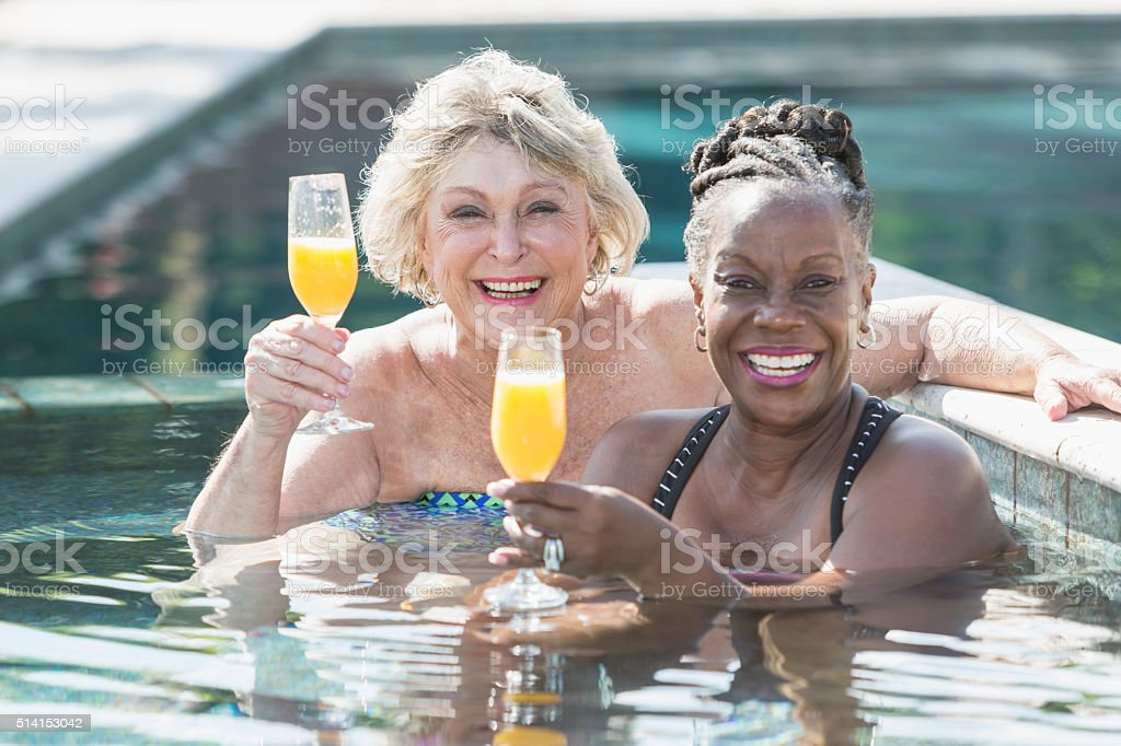 Two mature women enjoying cocktail in swimming pool Two multi-ethnic senior women enjoying drinks in swimming pool. These older women are young at heart, having fun, smiling and looking at the camera, holding their champagne glasses up for a toast. 60-69 Years Stock Photo