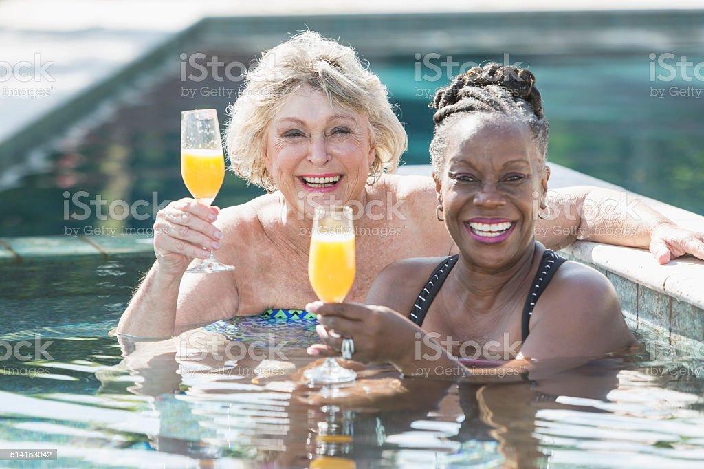 Deux femmes d'âge mûr savourant un cocktail dans la piscine - Photo