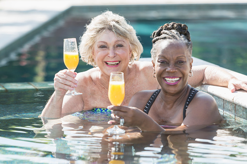 Two Mature Women Enjoying Cocktail In Swimming Pool Stock Photo - Download Image Now