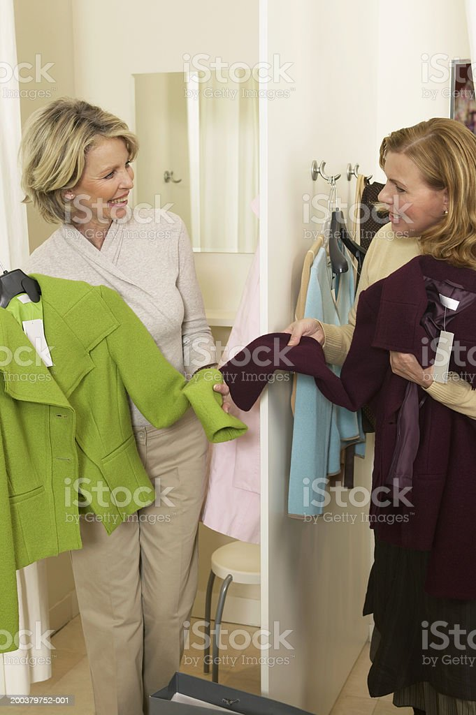 Two mature women holding jackets in clothes shop royalty-free stock photo