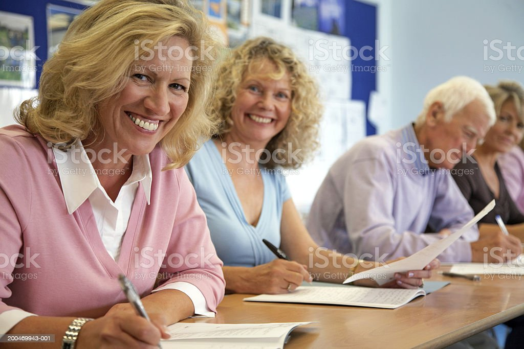 Two mature women in classroom, smiling, portrait royalty-free stock photo