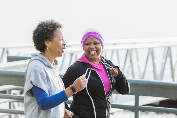 Two mature women jogging or power walking together stock photo