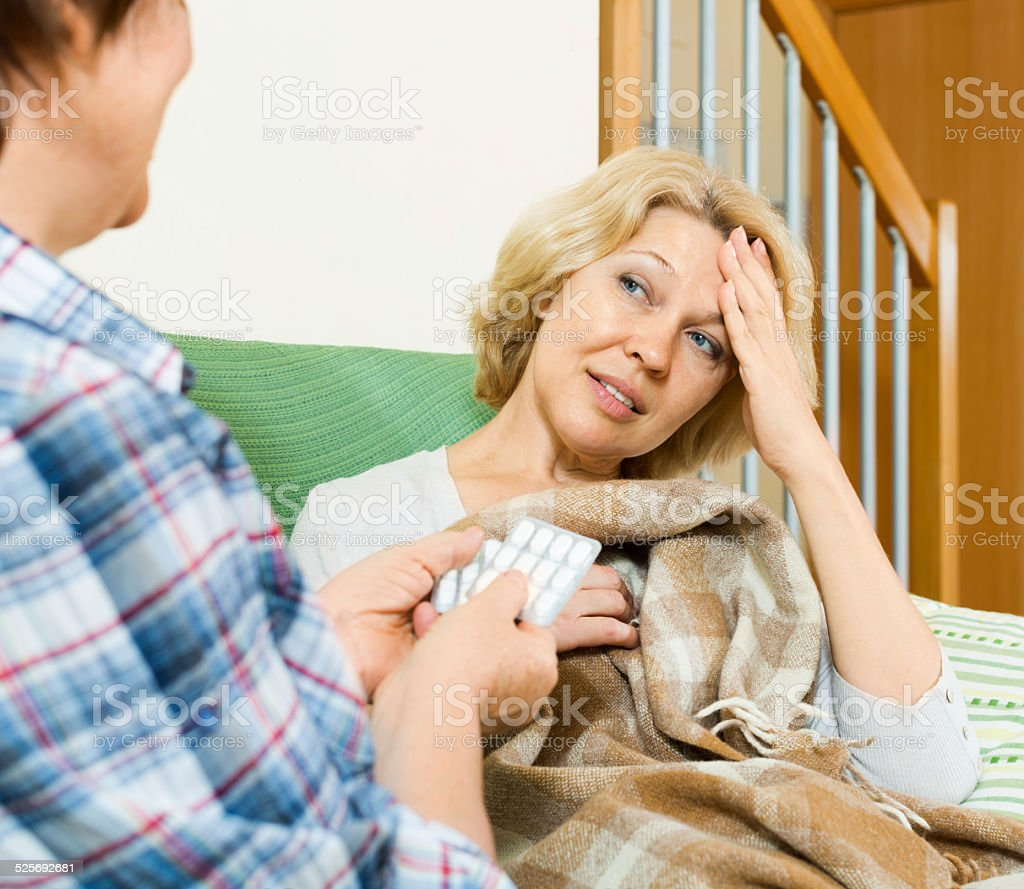 Two mature women with pill on couch stock photo