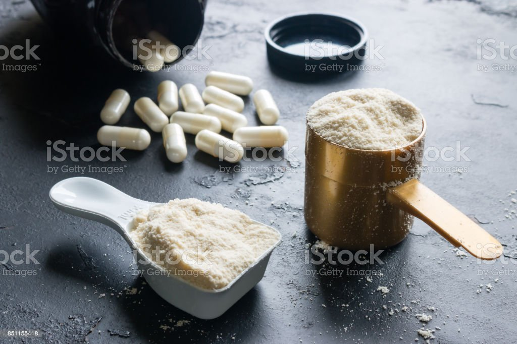 two measuring spoons of protein and creatine close-up on a black background stock photo