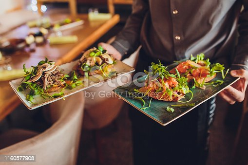 Two meat plate with salad leaves and summer salad in waiter's hand