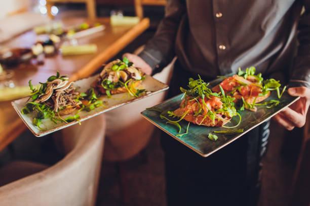 Zwei Fleischteller mit Salatblättern und Sommersalat in der Hand des Kellners. – Foto