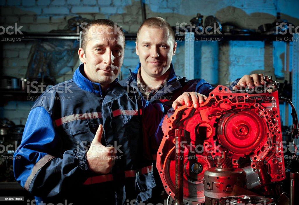 Two mechanics in repair shop royalty-free stock photo