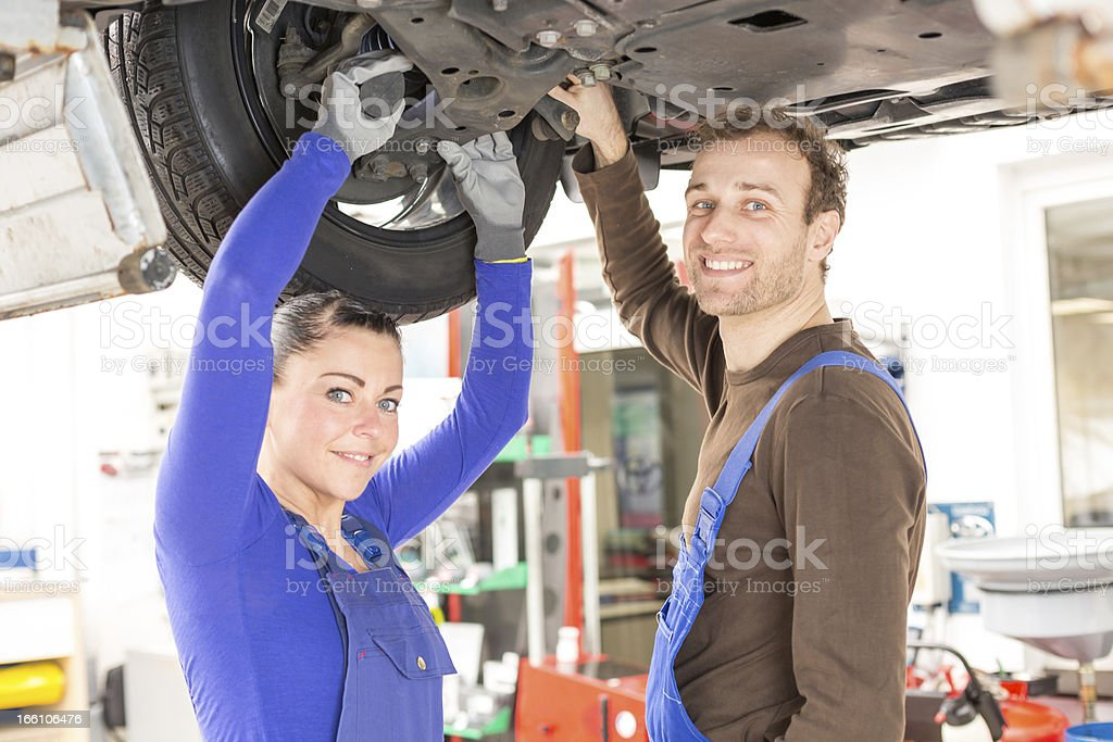 Two mechanics repairing a car in hydraulic lift royalty-free stock photo