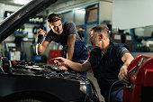 istock Two mechanics talking while repairing car's AC unit in auto repair shop. 1191771813