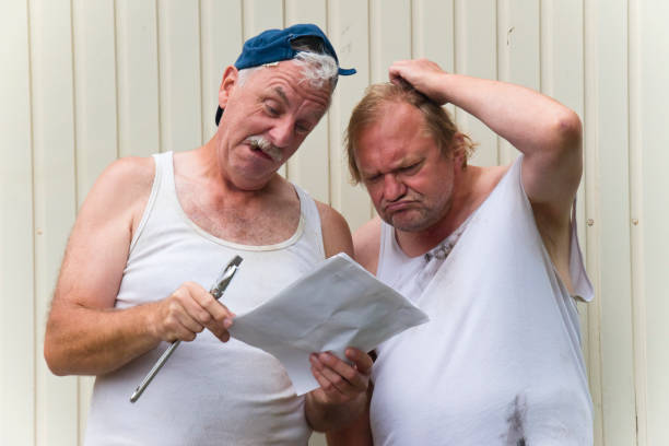 Two mechanics with difficult assembly instructions stock photo