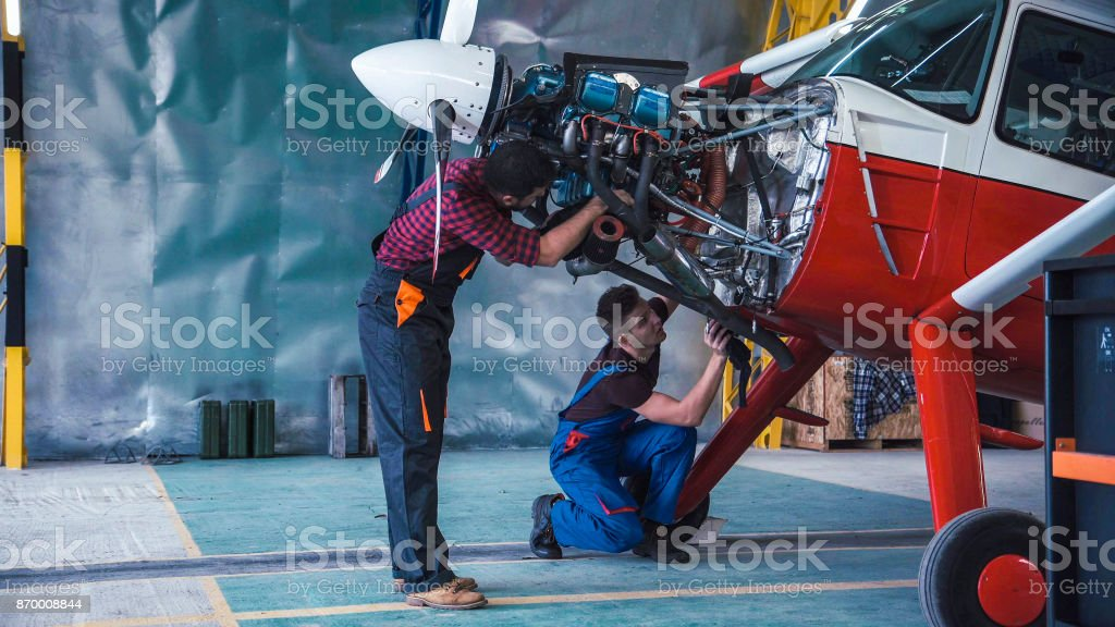 Two mechanics working on a small aircraft stock photo