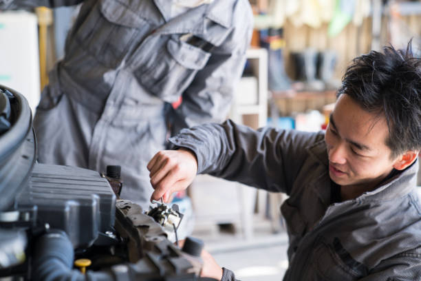 Two mechanics working together in an automotive repair shop stock photo