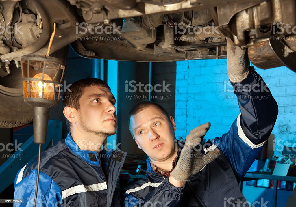 Two mechanics working under car in repair shop royalty-free stock photo