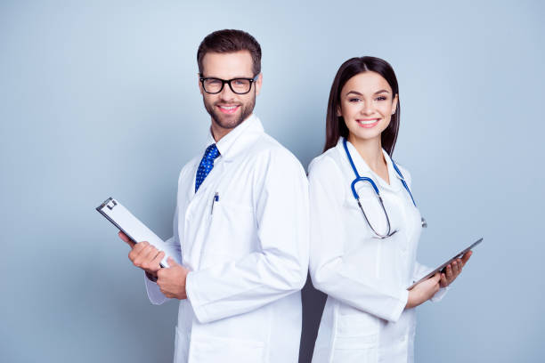 Two medic colleagues in white coats on pure background, holding clipboard and tablet. They are so successful, smile and work in team together stock photo
