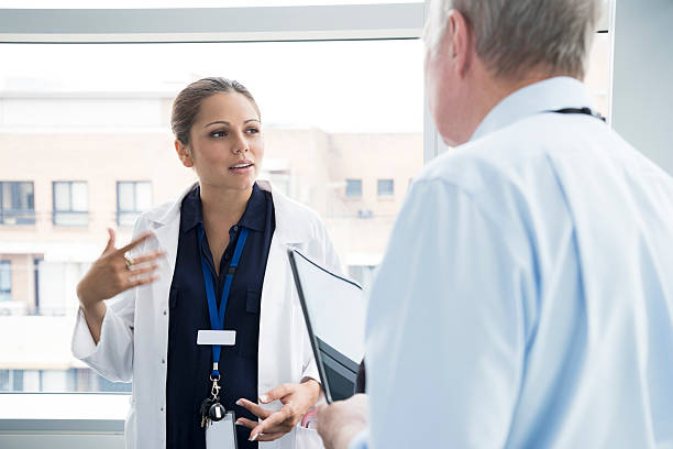 two medical consultants talking in hospital, woman gesturing - australian nurses stock photos and pictures