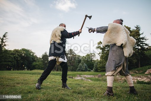 istock Two medieval fighting men with axes 1164556045