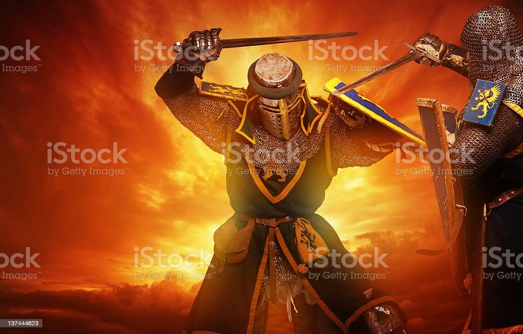 Two medieval knights fights against stormy sky background. stock photo