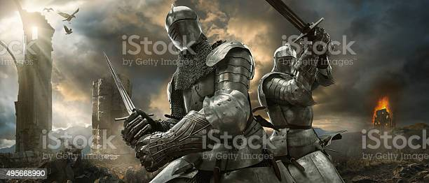 A dramatic image of two medieval knights in full suits of armour and chainmail holding swords in fighting positions close to stone monument ruins and burning castle in the background. The knights are on a high battle ground under a dramatic cloudy evening sky with shafts of sunlight and ravens.