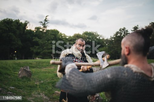 istock Two medieval men fighting with axes outdoors 1164547580