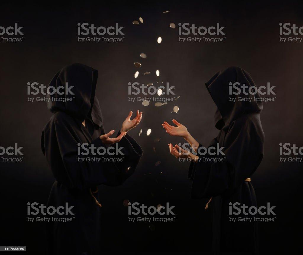 Dois monges medievais e moedas caindo do céu - foto de acervo