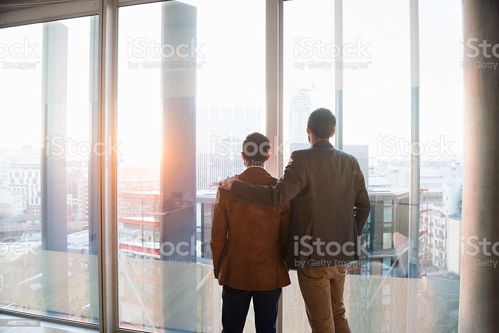 Two men admiring city through window stock photo