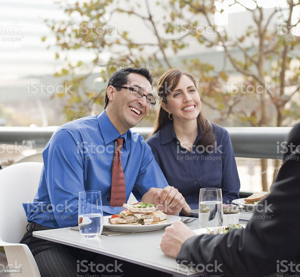 Two men and a woman sit at cafe for lunch. royalty-free stock photo