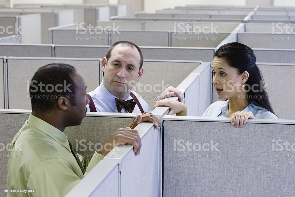Two men and woman talking in office cubicle foto de stock libre de derechos