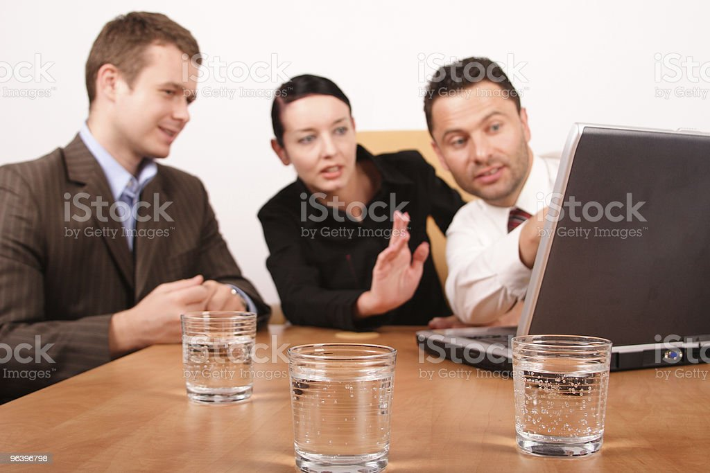 Two men and woman working on project with laptop - Royalty-free 25-29 Years Stock Photo