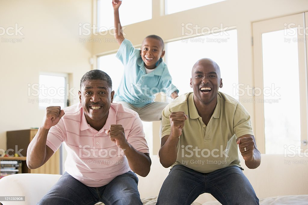 Two men and young boy in living room cheering stock photo