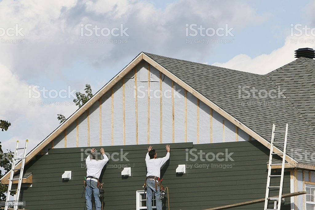 Two men applying green paneling to a house stock photo