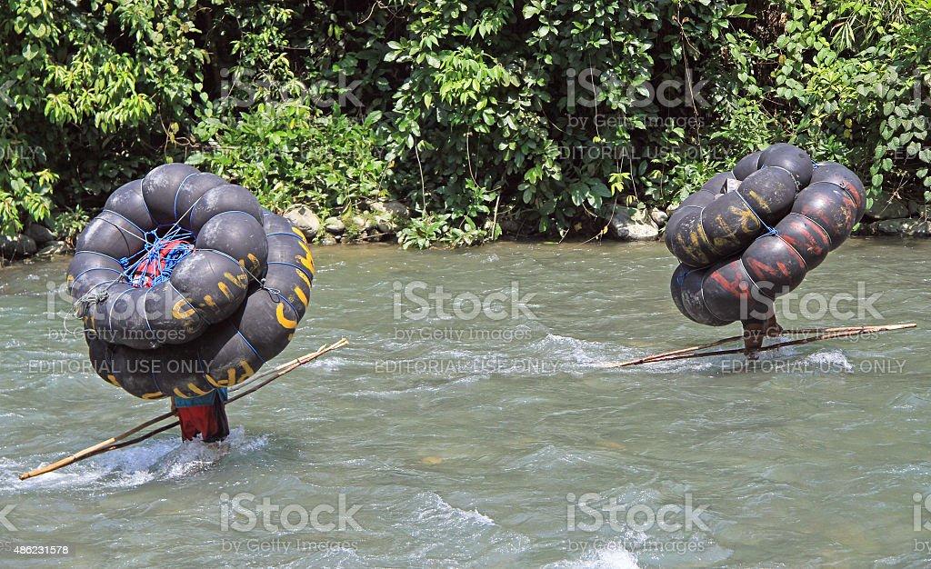 two men are carrying tube, Bukit Lawang stock photo