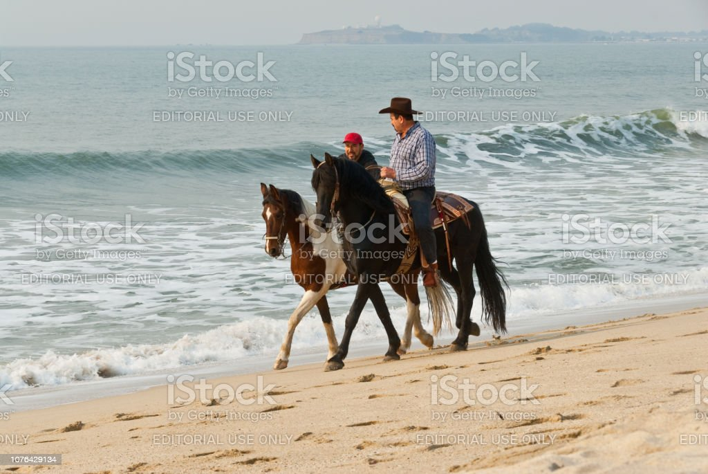 Horseback Riding at the Pacific Ocean stock photo