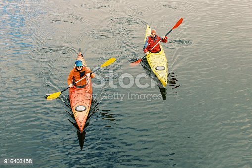 Two men are kayaking along the river.