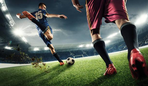 zwei männer spielen fußball und sie konkurrieren miteinander - fußball wettbewerb stock-fotos und bilder
