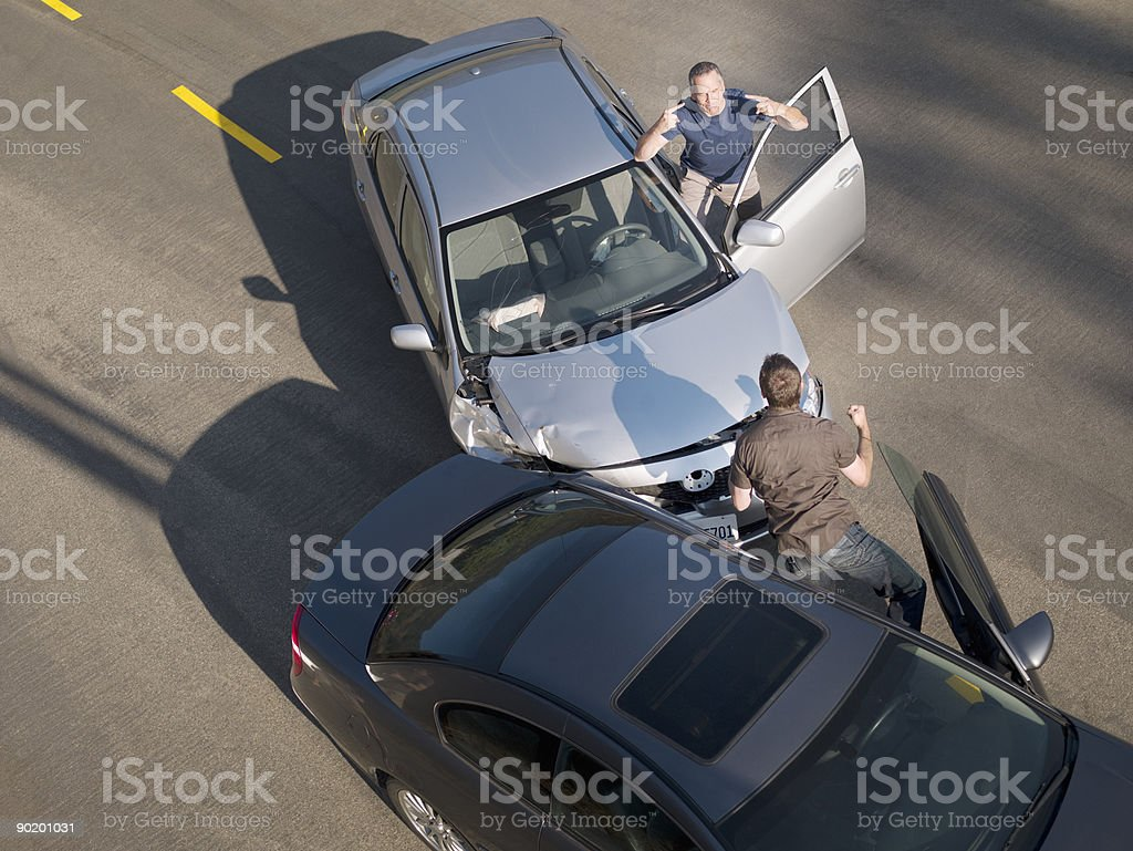 Two men arguing about damage in car collision stock photo