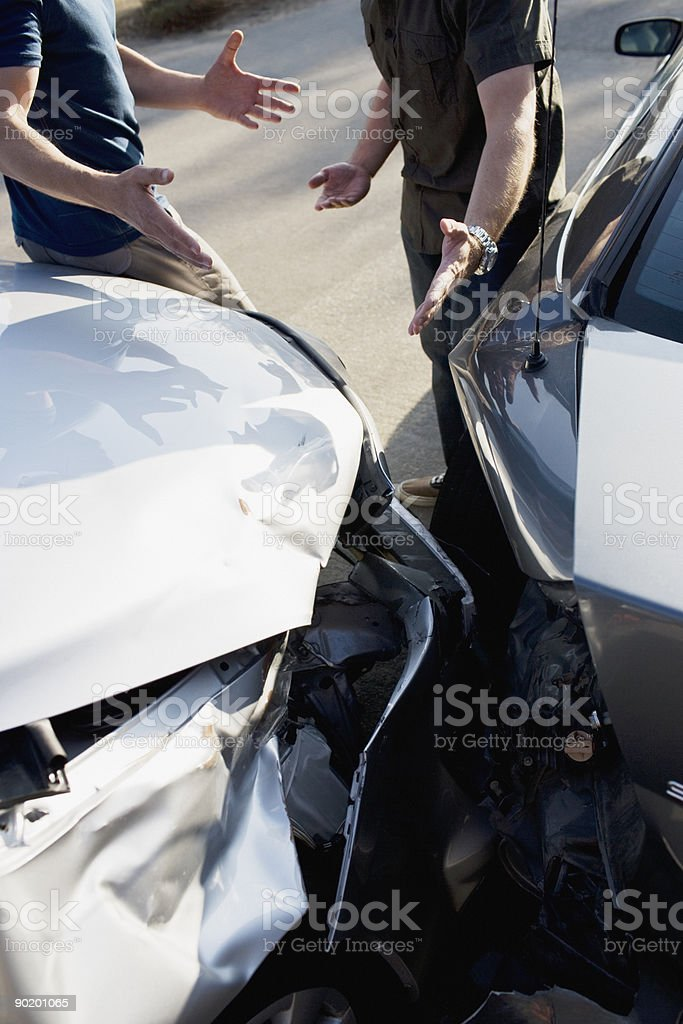 Two men arguing about damaged cars royalty-free stock photo