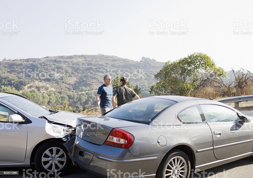 Two men arguing about damaged cars stock photo