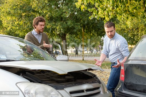 1047083324 istock photo Two men arguing after a car accident on the road 619633098