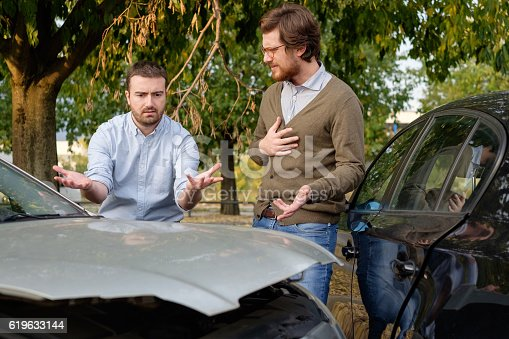 1047083324 istock photo Two men arguing after a car accident on the road 619633144